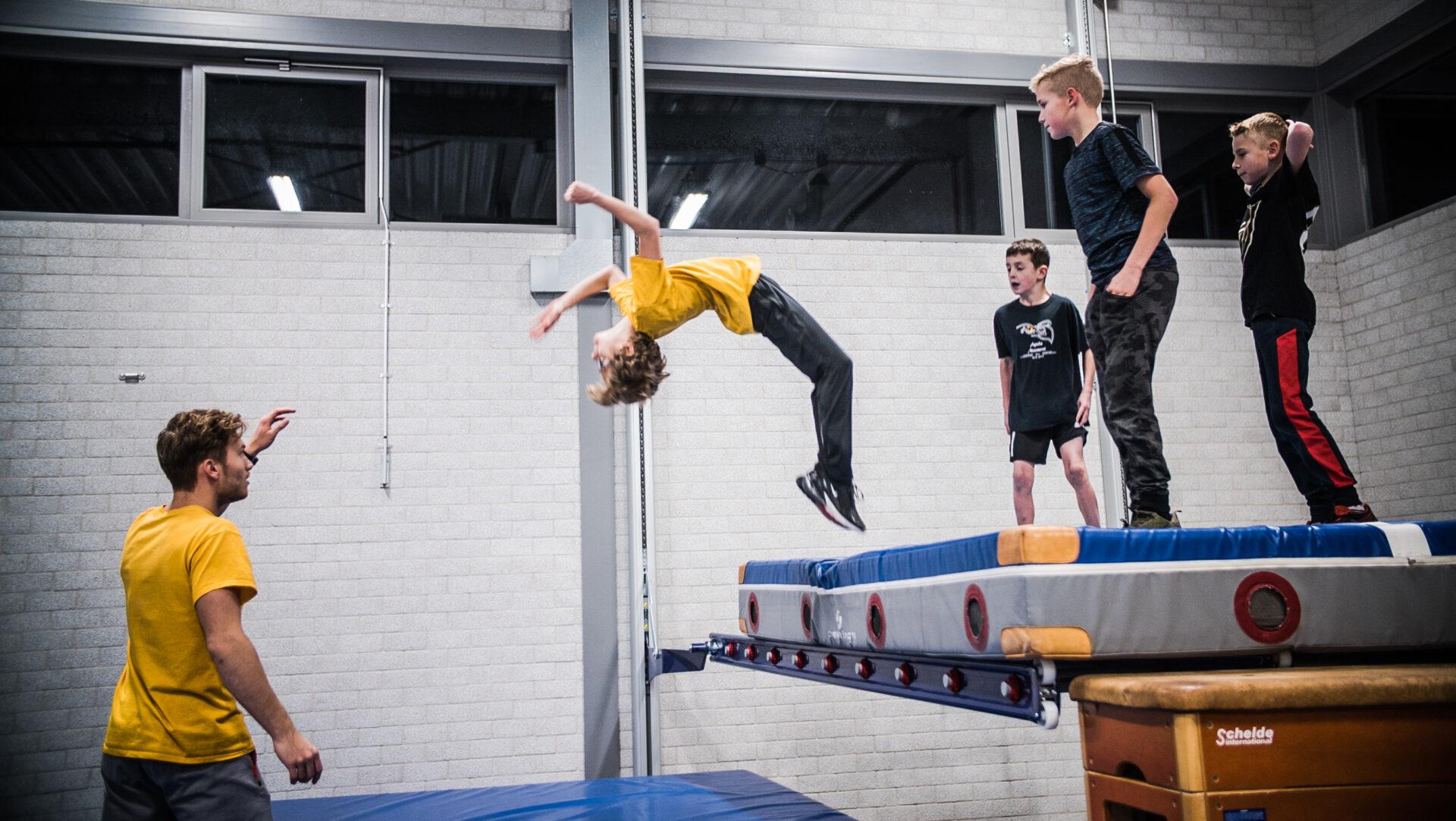 Trainer helpt met een backflip bij Freerun lessen