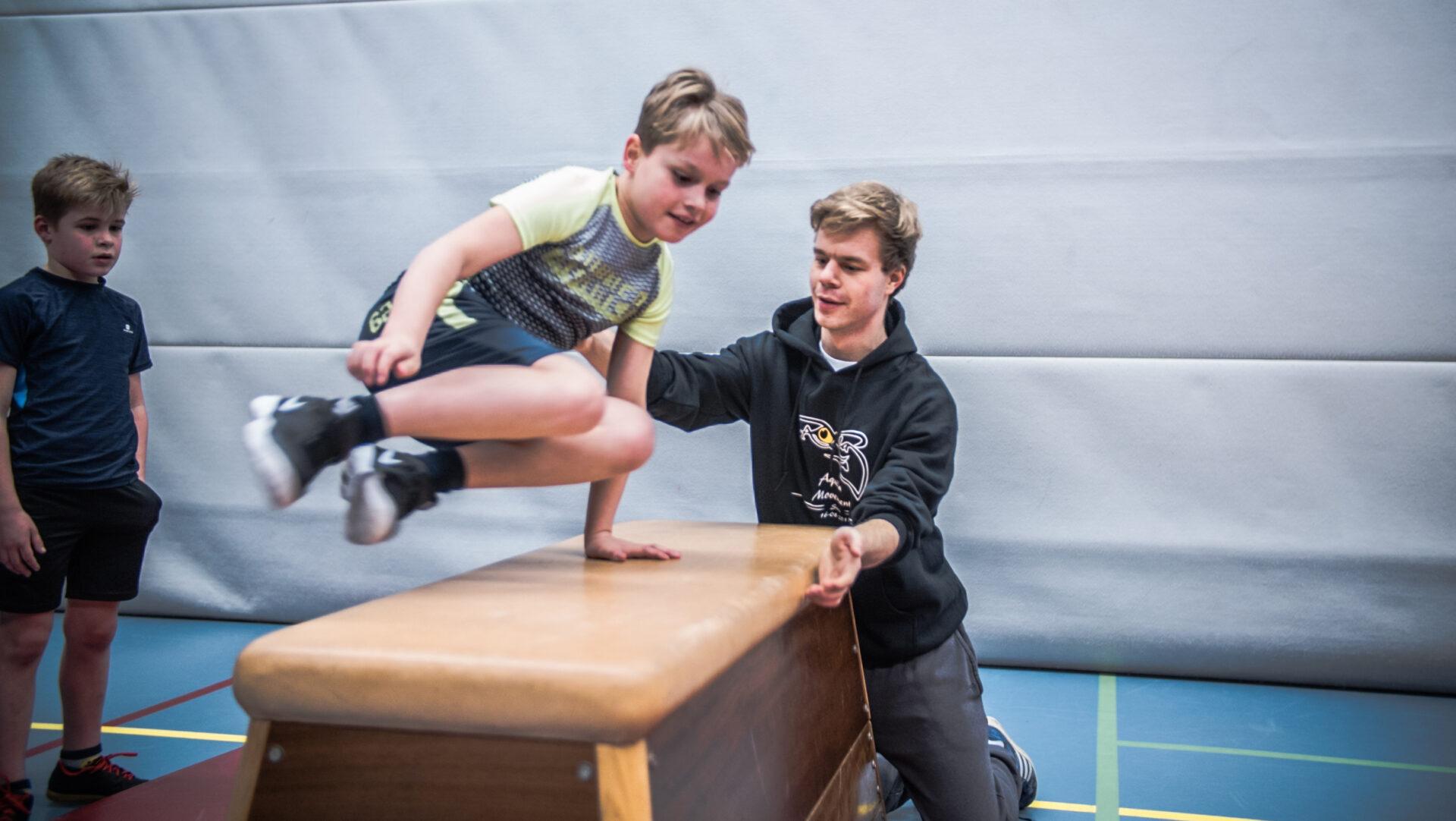 Trainer helpt kind met freerunnen bij freerun les